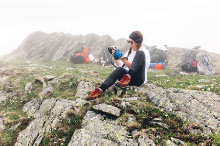 A girl travels in the mountains taking pictures with a camera, camping backpack background. The concept of adventure, lifestyle hikes.