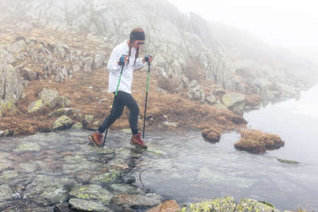 The girl travels through the river in a rocky terrain in foggy weather. Wild landscape with clouds. The concept of lifestyle, adventure, enjoyment and relaxing hikes.