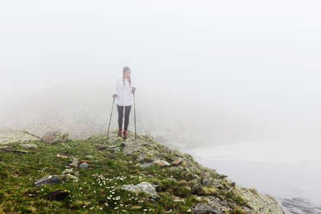 The girl traveled for a walk in the rocky terrain in foggy weather. Wild landscape with clouds. The concept of lifestyle, adventure, enjoyment and relaxing hikes.