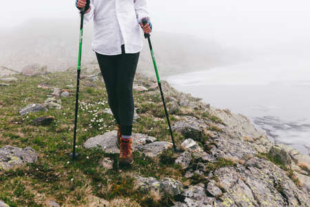 The girls legs against the background of the landscape in foggy weather during a walk. Wild nature in the clouds. The concept of a way of life, adventures, pleasures and relaxing hikes.