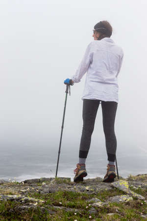 Portrait of a girl from behind on a background of a landscape in foggy weather during a walk. Wildlife, the concept of lifestyle, adventure, a passion for travel, walking and hiking. Stock Photo