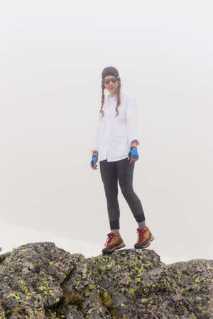 Tourist woman walking along a rocky terrain in foggy weather. Lifestyle summer vacation by nature, the concept of adventure outdoors, hiking and travel.