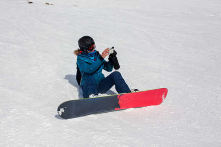 Girl snowboarder in helmet and mask takes pictures using smartphone, while riding snowboarding. Connectivity mobility lifestyle technology. Travel Lifestyle sport and extreme, adventure activities. Archivio Fotografico