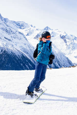 Girl snowboarder in helmet and mask talking on smartphone. Connectivity mobility technology. Travel Lifestyle sport and extreme, adventure activities. Ski resort in the mountains vacations.