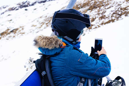 Sports girl snowboarder in helmet and mask takes pictures using smartphone, sitting on cable way. Connectivity mobility lifestyle technology. Travel Lifestyle sport and extreme, adventure activities. Archivio Fotografico