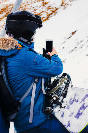 Sports girl snowboarder in helmet and mask takes pictures using smartphone, sitting on cable way. Travel Lifestyle sport and extreme, adventure activities. Holidays in the mountains at a ski resort.
