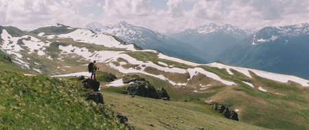 Adventurous man is standing on top of the mountain and enjoying the beautiful view Hiking Traveling alone, healthy lifestyle active vacations trail running outdoor. Adventure traveling rocky mountains