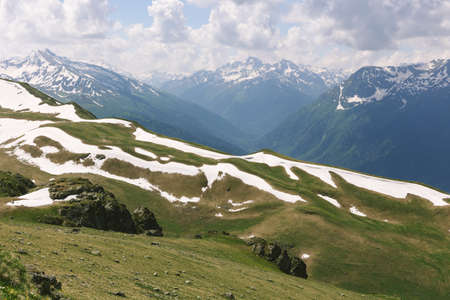Panoramic view of idyllic mountain scenery in with fresh green meadows in bloom on a beautiful sunny day in springtime stones among the grass on top of the hillside near the peak of the mountain range Archivio Fotografico