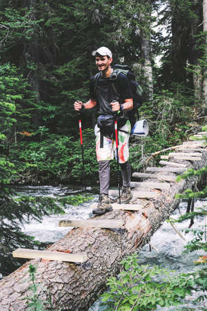 Man Traveler with backpack hiking the bridge over a river the expedition, Travel Lifestyle concept. Hipster forest on background Summer journey vacations outdoor. Adventure extreme sport recreation.