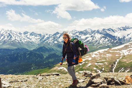 Traveler backpacker on mountains cliff hiking enjoy landscape. Hair fluttering in the wind, cheerful positive hipster girl. Travel Lifestyle concept adventure active vacations outdoor aerial view.