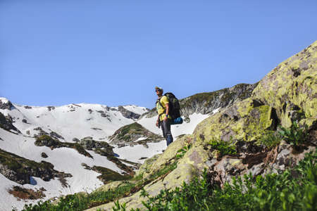 Young male conqueror of the summit wearing climbing clothing and a backpack, looks at horizon with a fascinating view against the background of snow-covered rocks and a blue sky. Advertising space