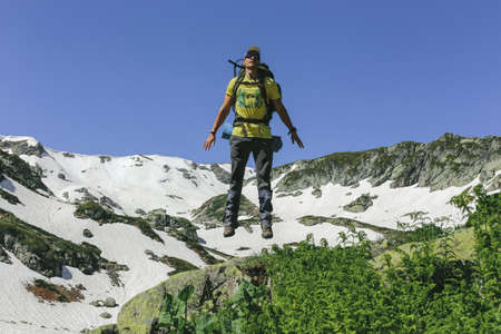 Man traveler outfitted with sportswear and backpack hovered in air while jumping against background of snow-covered rock and blue sky. Concept of joy conquering peaks and tourism. Advertising space