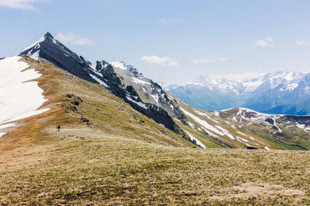 Mountain hike travel hiker man trekking in Switzerland Alps mountains landscape background. Panoramic banner of hiker on adventure trek. Active lifestyle adventure vacations.