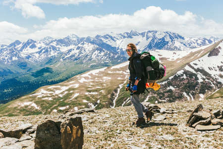 Positive young woman tourist climber with backpack sunglasses climbed to the top of the mountain against the backdrop of a green valley of snow-capped mountain ranges. Travel Lifestyle adventure.