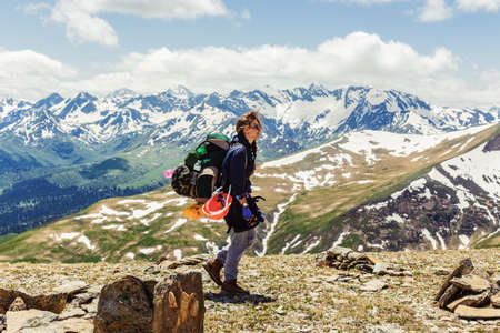 Side view of young tourist girl with large backpack walking along top of mountain with wildflowers on background of charming view snow-capped mountains. Concept of mountaineering. Lifestyle adventure. Archivio Fotografico