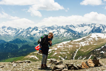 Woman traveler hiking in mountains with backpack adventure travel healthy lifestyle active summer vacations explore. Cheerful positive hipster girl. Lifestyle concept sport outdoor.