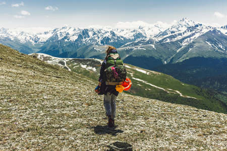 Woman traveler hiking in mountains with backpack adventure travel healthy lifestyle active summer vacations. Explorer climbed to the top of the ranges over the green valley and snow-capped peaks.