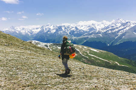Rear View of a female hiker with a backpack standing on top of the mountain. Woman traveler hiking adventure travel healthy lifestyle active vacations. Explorer climbed to the top of the ranges Archivio Fotografico