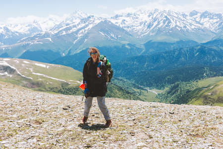 Young happy Girl hair fluttering in the wind hiking Traveler with backpack and sunglasses at rocky mountain landscape. Travel Lifestyle concept adventure summer active vacations outdoor.