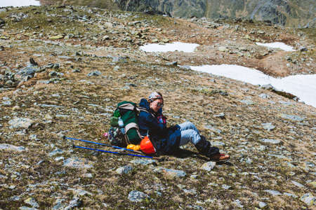 Young girl tourist mountaineer in special clothes and backpack sitting on a mountain surface and resting after conquering the summit. Concept of outdoor activities