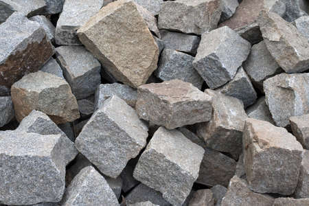 A large pile of boulder rocks. Stones for the construction industry. Stone background, dark gravel stone texture, granite.