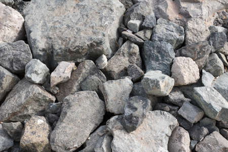Large Pile of Gray Boulder Rocks. Stones for the construction industry. Stone background, dark gravel pebbles stone texture, granite.