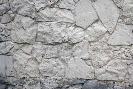Wall decorative stone texture background painted white. Masonry as a cladding of exterior buildings and structures.
