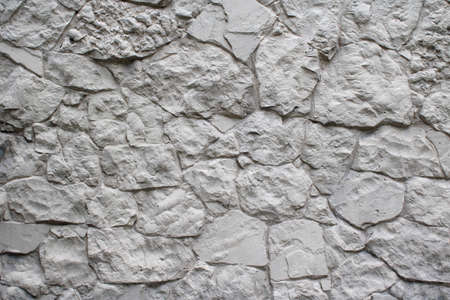 Natural facade wall stone decoration background texture painted white. Modern granite stone wall masonry as a cladding of exterior buildings and structures. Banque d'images