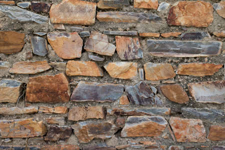 Wall texture background stone. Grunge facing coarse, rough stone or rock texture of mountains. Aged grungy stonework city. Damage front decor house.