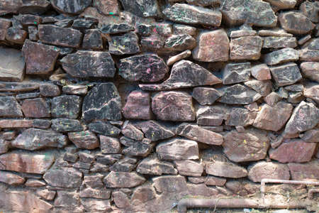 Grunge background stone wall texture. Rough old stone or rock textured of mountains. Coarse facing, grungy aged stonework city. Front antique decor house. General layout of stone masonry.