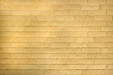 Modern yellow background wall texture from decorative bricks. Abstract light masonry surface of building blocks. Simple building in rustic style, rough building house, horizontal architecture wallpaper. Stockfoto