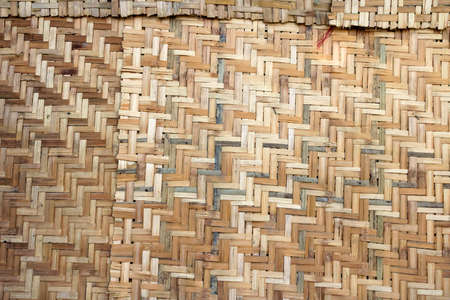 Woven palm wood pattern. Bamboo brown straw mat, abstract background texture wicker composition. Weaved mat from dried palm leaves. Interlocking of coconut leaves.