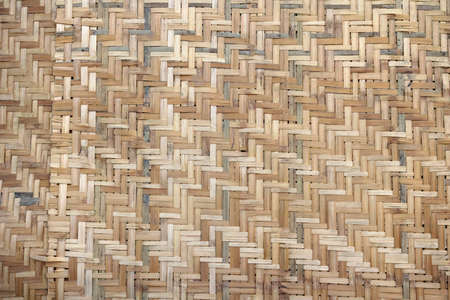 Woven palm wood pattern. Handcraft woven bamboo brown straw mat, abstract background texture wicker composition. Weaved mat from dried palm leaves. Interlocking of coconut leaves. Standard-Bild