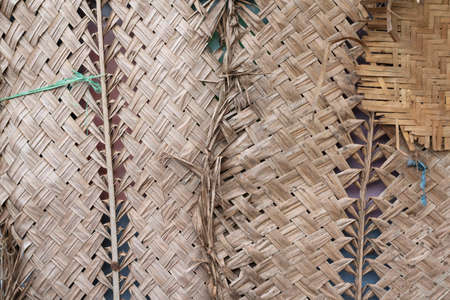 Palm tree woven pattern. Handmade wicker bamboo. Bamboo straw mat. Abstract background texture wicker wall. Interlacing of coconut leaves. Wicker mat made of dried palm leaves. Bamboo wickerwork.
