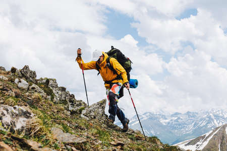 Male tourist with a large backpack and mountain poles climbs to the top of the mountain against the backdrop of snow-capped mountain ranges on the spring day. Concept of travel and leisure