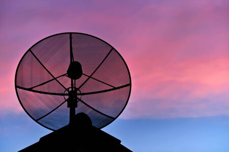 satellite dish silhouette in evening sky.