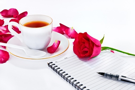white cup of coffee with red roses and notebook on white background