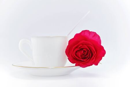 white cup of coffee with red rose on white background