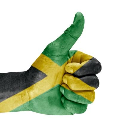 Bandera de Jamaica en los pulgares para arriba la mano aisladas sobre fondo blanco photo