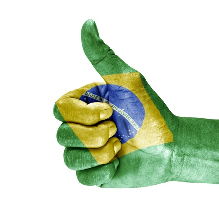 Flag of brazil on thumb up hand isolated on white background.
