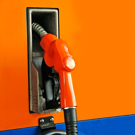 unleaded: Orange fuel pump in a gas station.
