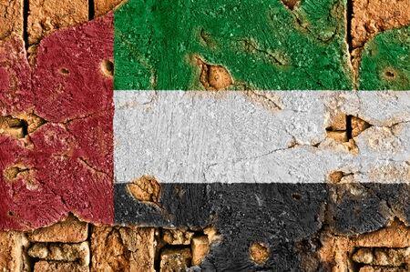 Grunge flag of United Arab Emirates on old wall background.