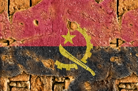 Grunge flag of Angola on old wall background.
