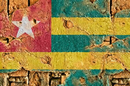 Grunge flag of Togo on old wall background.