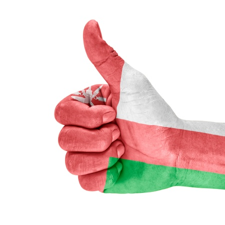 oman background: Flag of Oman on thumb up hand with a white background. Stock Photo