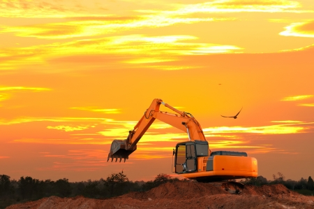 Excavator at construction site with golden sky sunset  in the evening photo