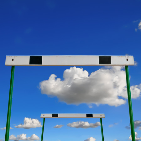 Hurdles track with a blue sky and cloud background.