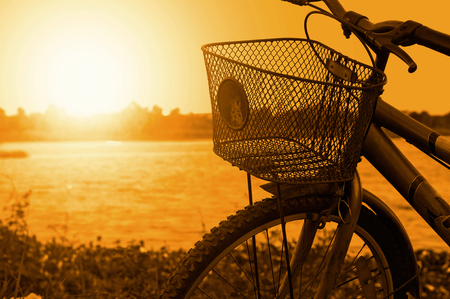 Vintage old bicycle on riverside in the evening. Stock Photo