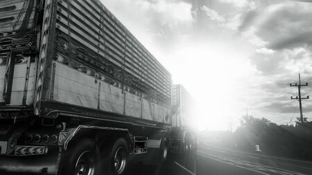 Truck on asphalt road under sky with clouds and sunlight.