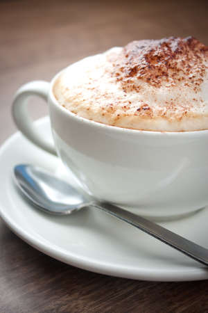 capuchino: A cup of Cappuccino with a spoon